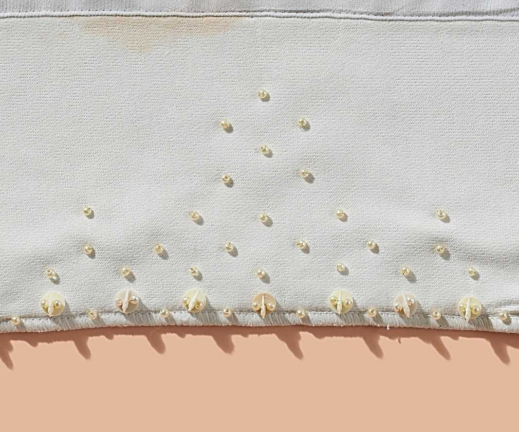 Deborah Prior,  Domestic White Work  (detail) ,  2019 ,  nappy liners, Squatter sheep tokens, beads ,  3 panels each approx. 320 x 320 mm. Photo: Sam Roberts.