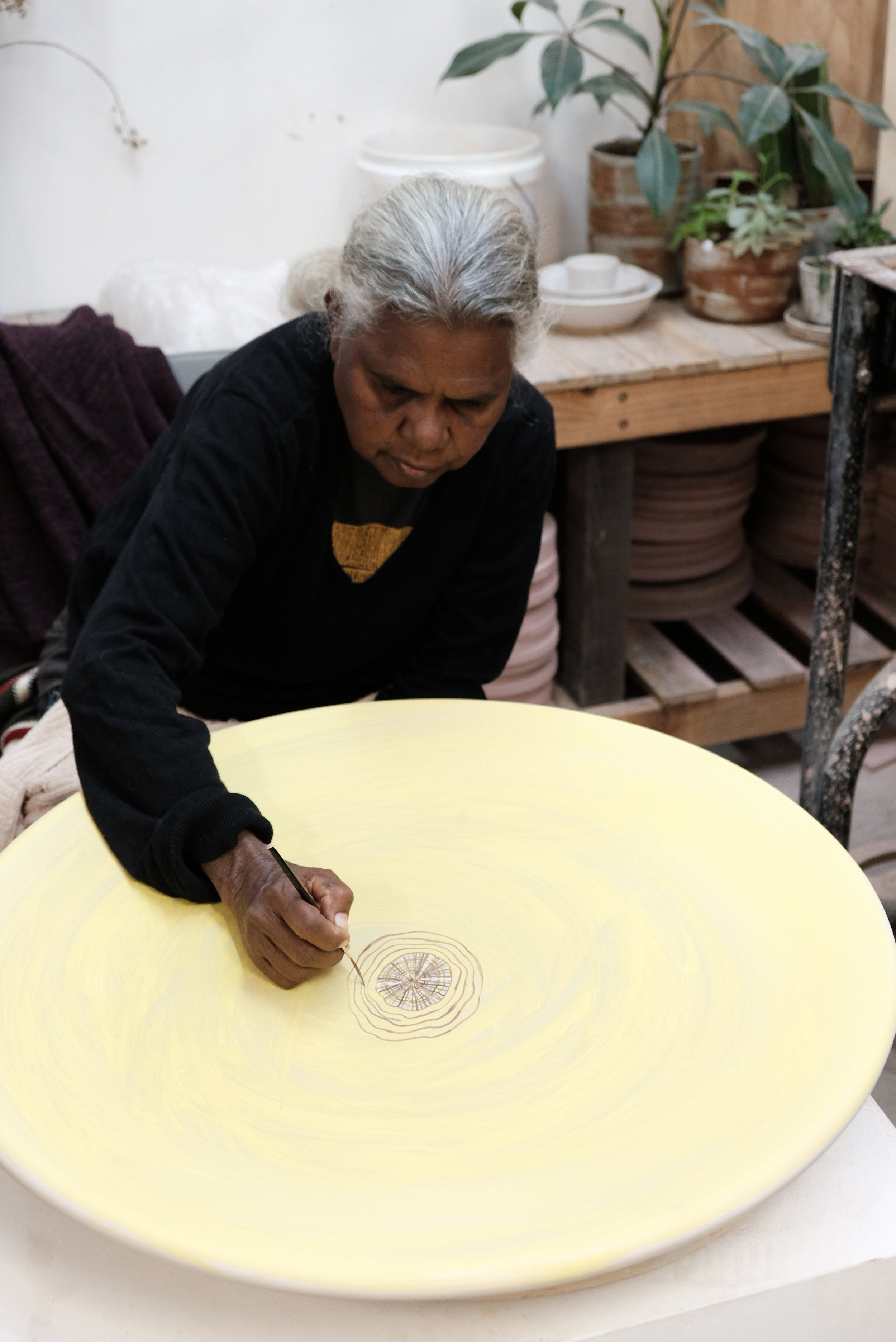 Regina painting in ochre on platters created by Mark Heidenreich. Photo courtesy of JamFactory.