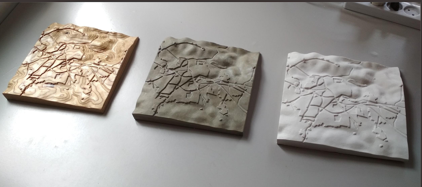 Samples of the 3-dimensional topographic pieces based on British survey maps. Left-to-right: CNC cut plywood, concrete cast and plaster cast.
