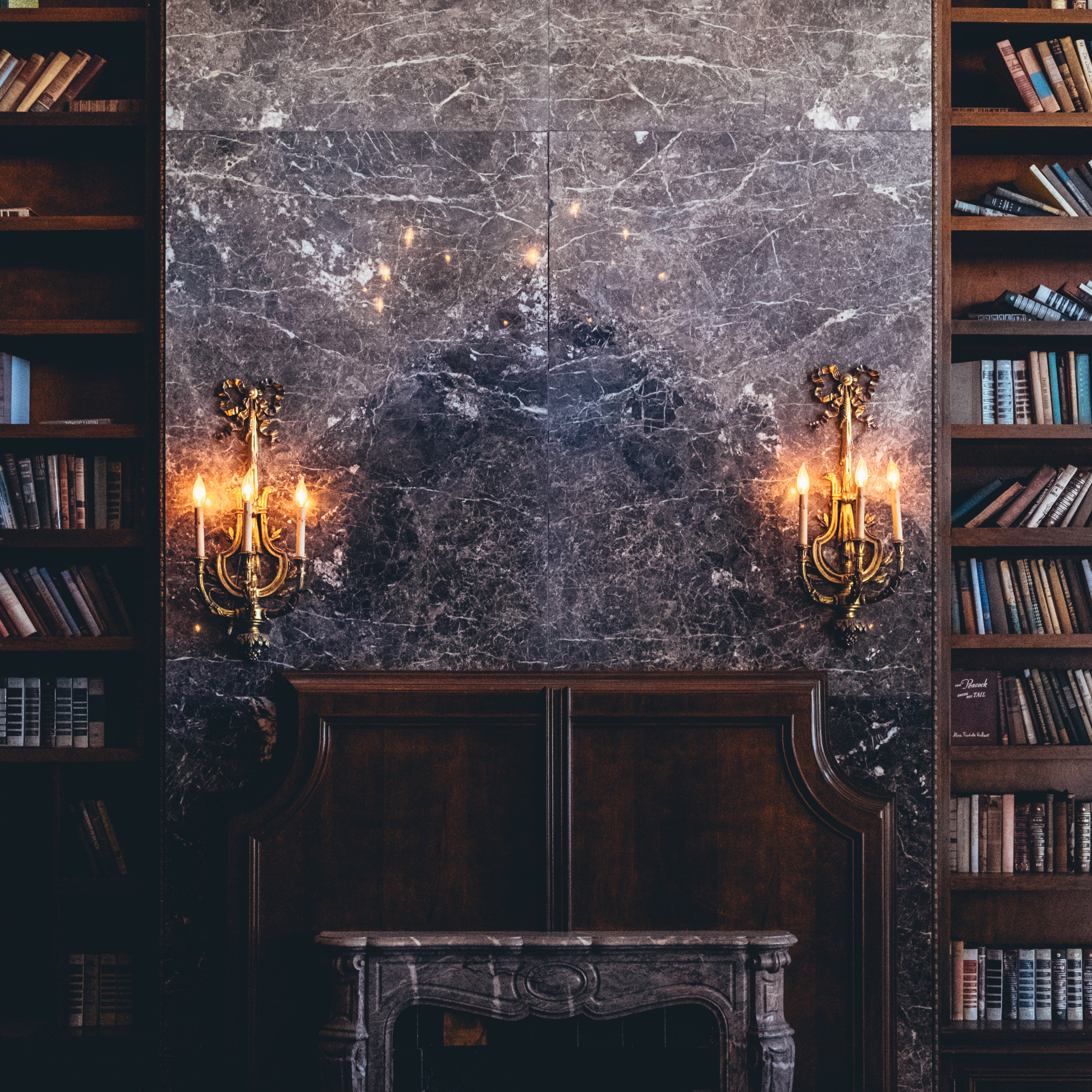 The library is my favorite room. Two stories of books and mustard velvet curtains hiding stained glass windows, chandelier, six red velvet reclining loungers, one random statement chair with marble inlay, and a fireplace.
