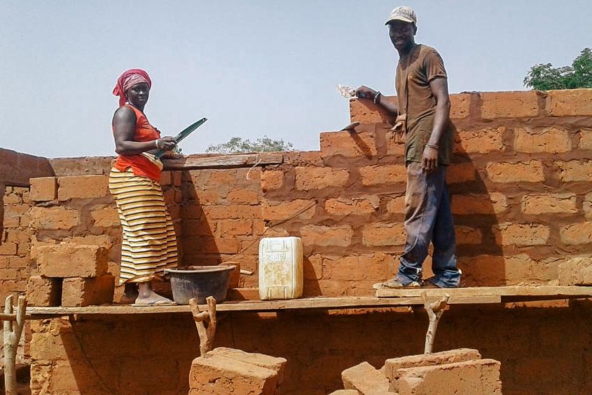 Community members laying bricks
