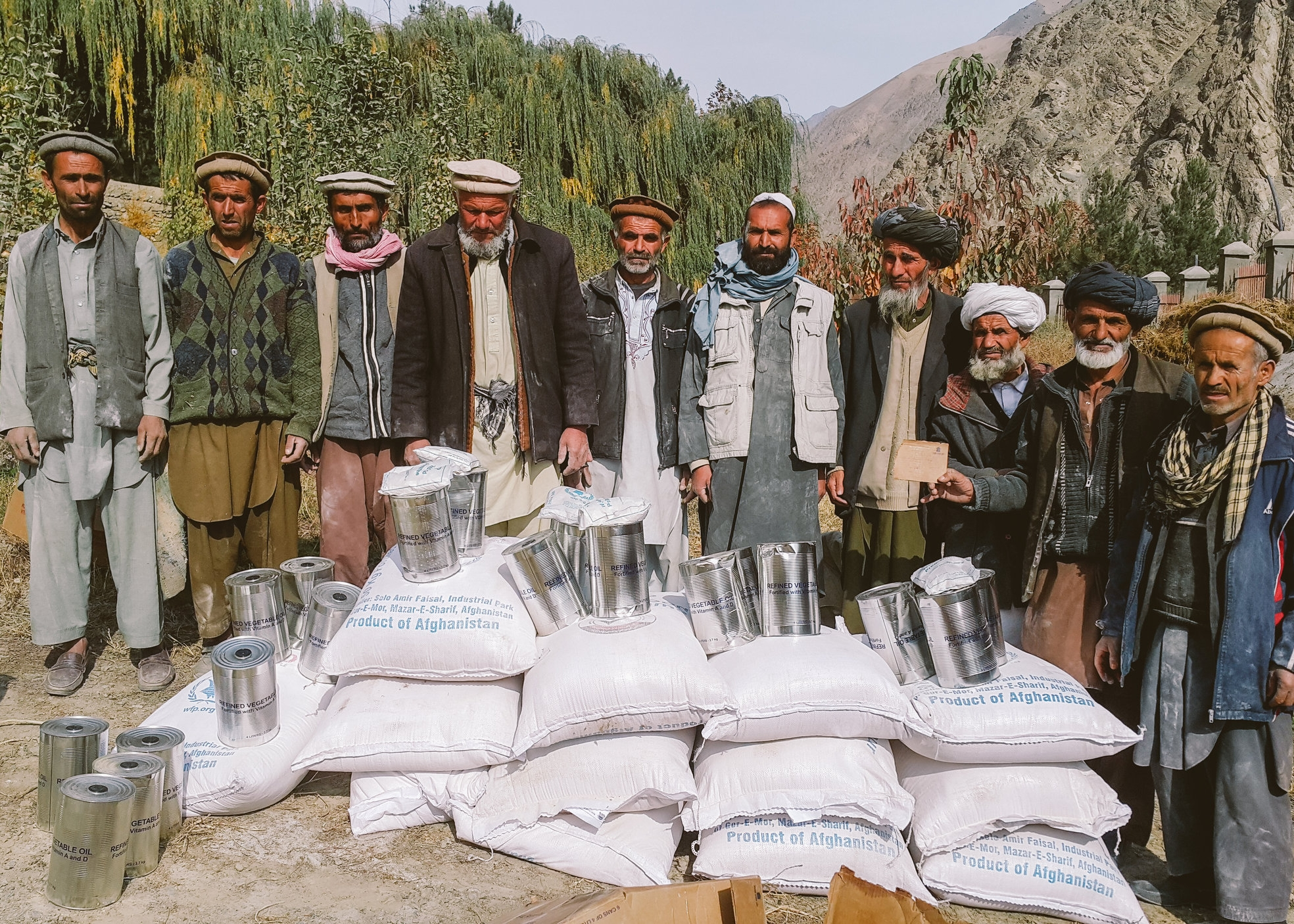 Workers receiving cooking oil and wheat in exchange for their work rehabilitating a local road and irrigation canal
