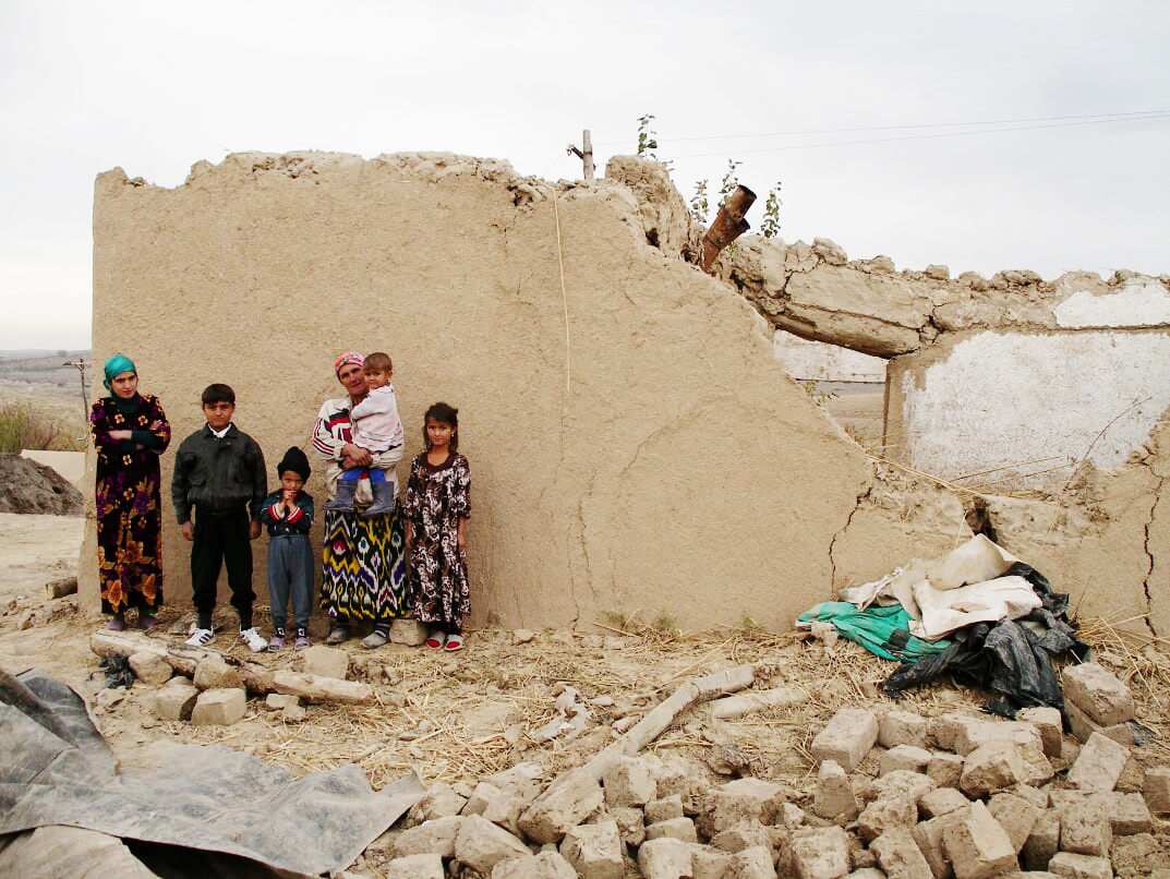 Family with the ruins of their home