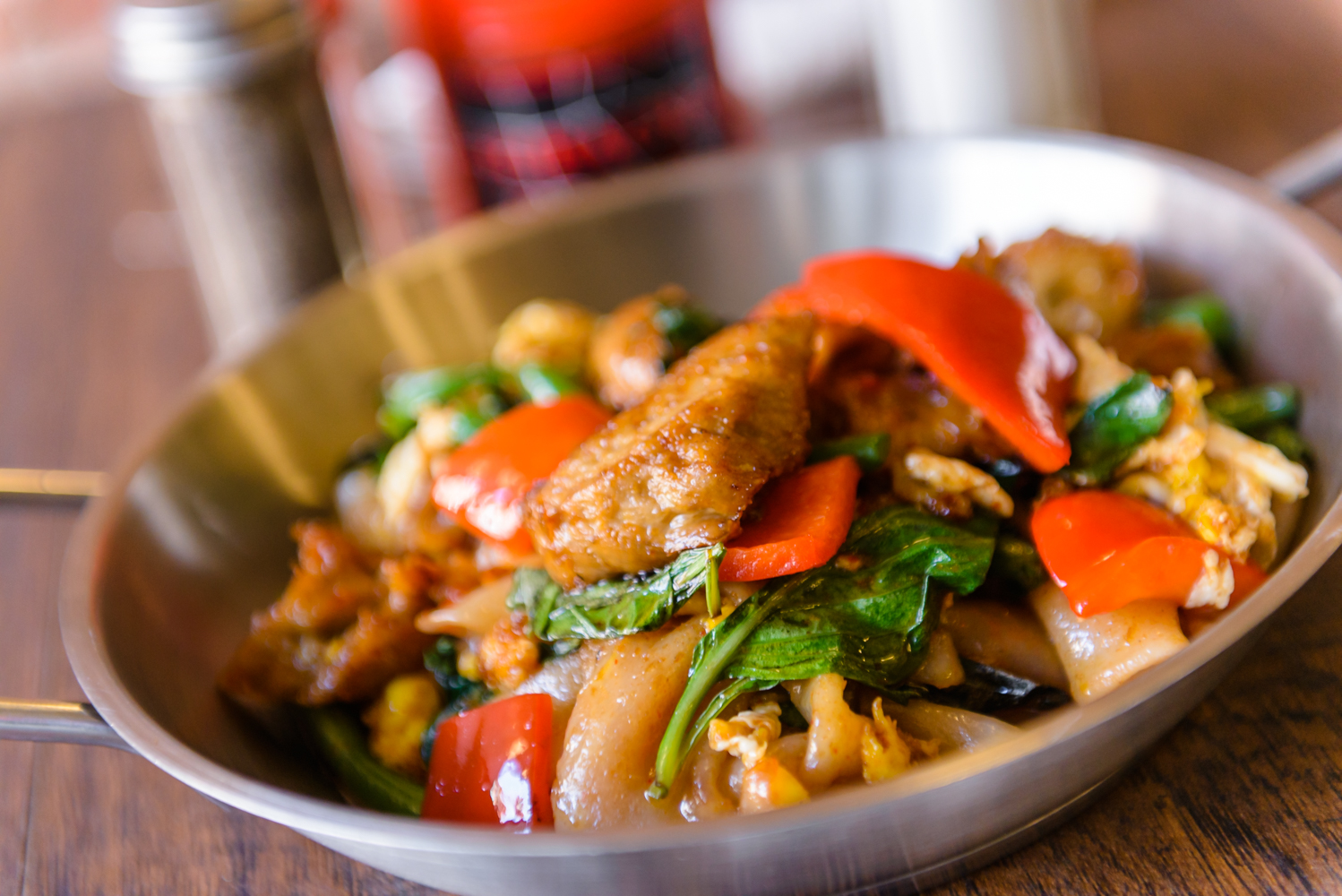 Sauteed Drunken Noodles served with flat noodles, spicy chili paste, basil, onion, bell pepper, and string beans