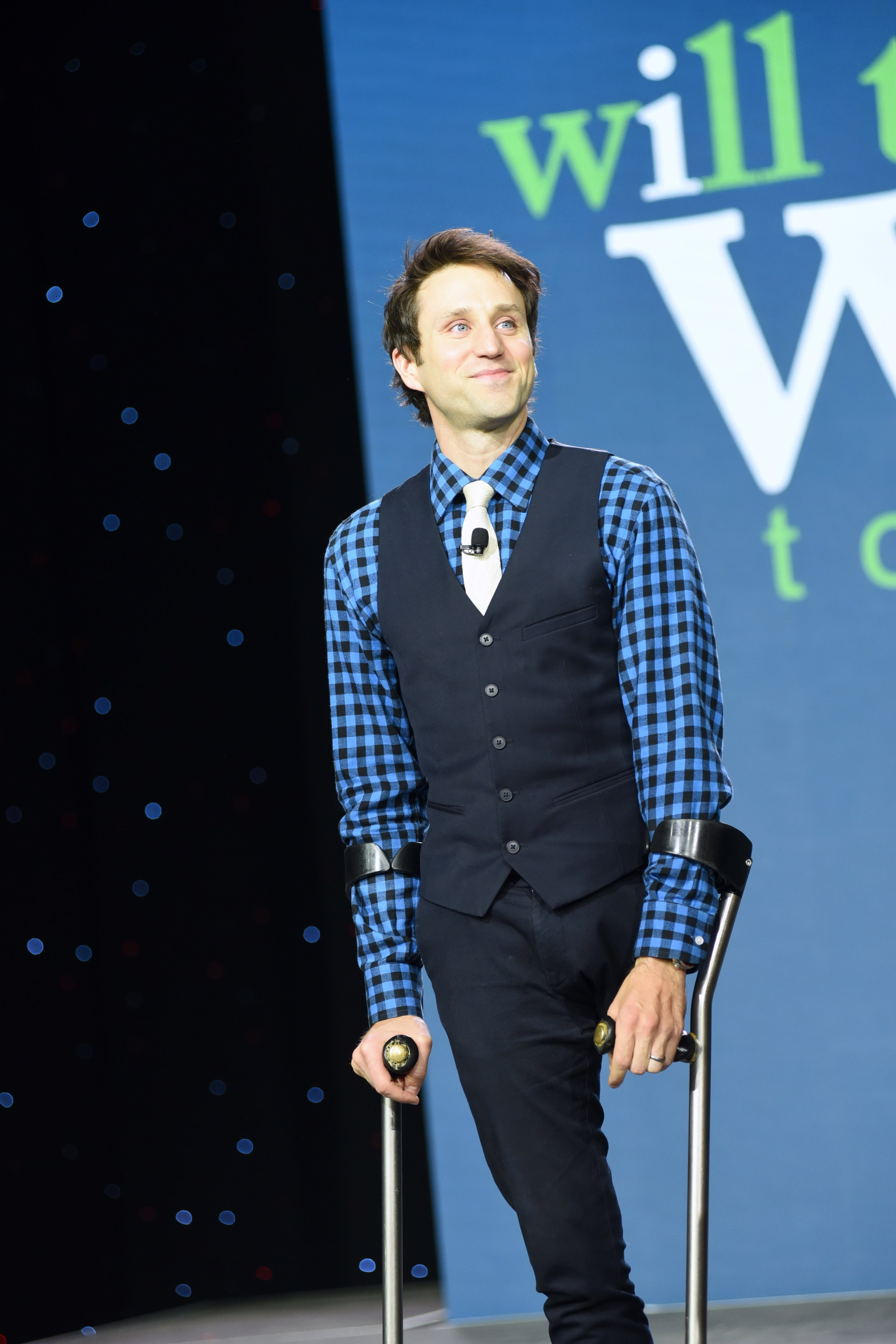Josh Sundquist smiles while giving a motivational speech