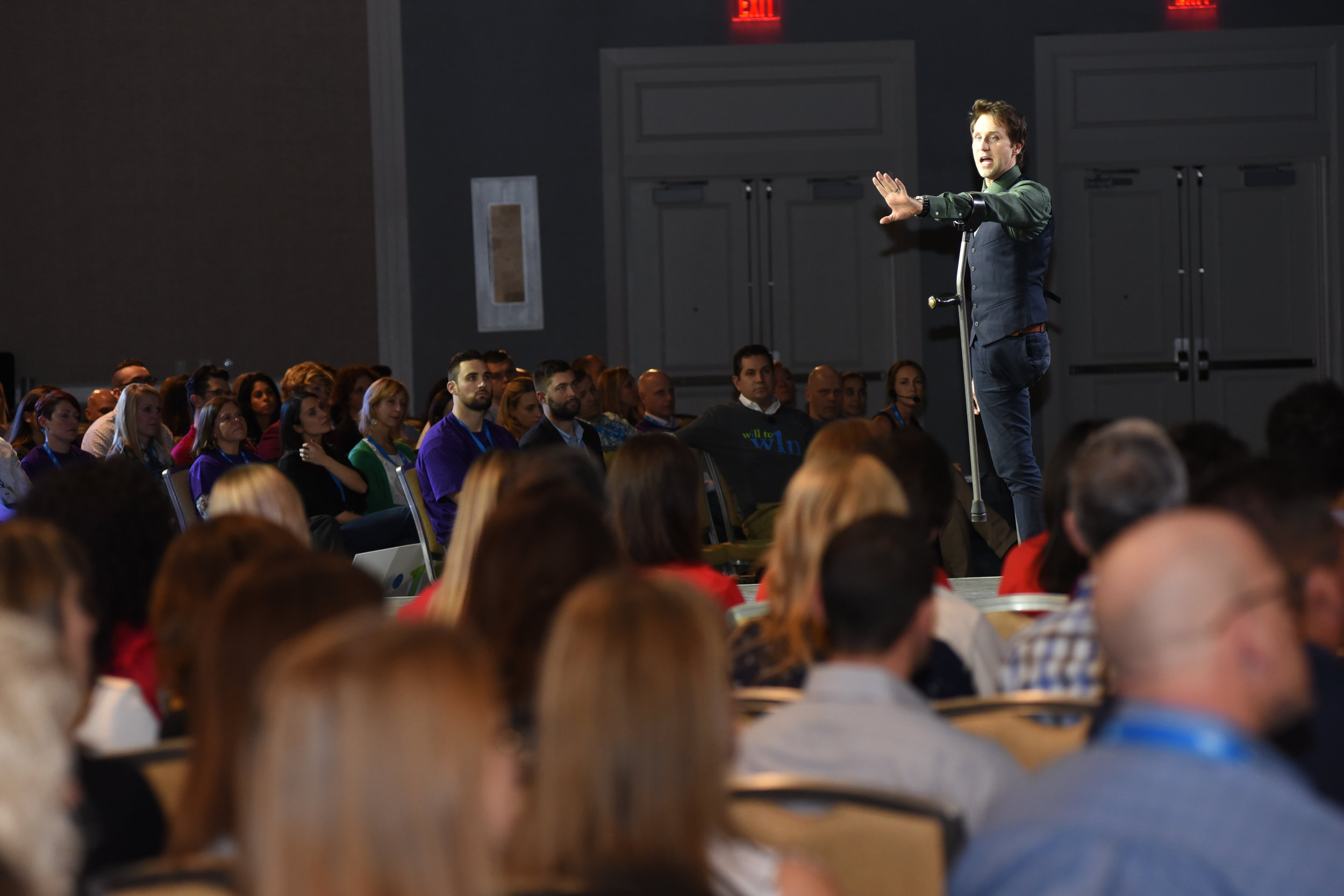 Inspirational speaker Josh Sundquist stands in the center of an audience, gesturing