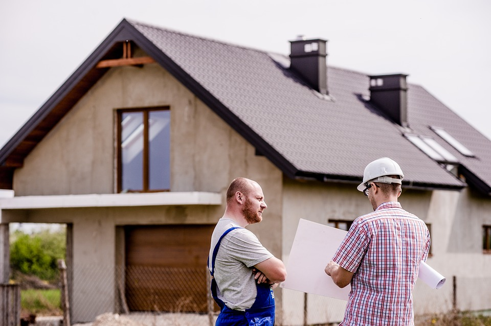 Two construction workers talking outside a house