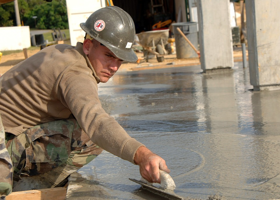 Construction worker smoothing out concrete
