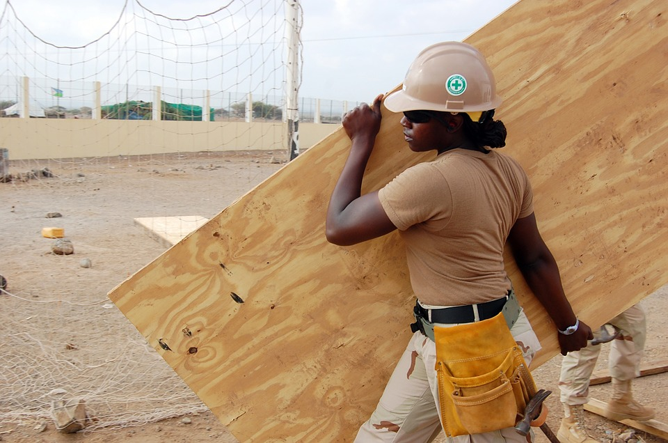 Construction woman carrying a piece of plywood