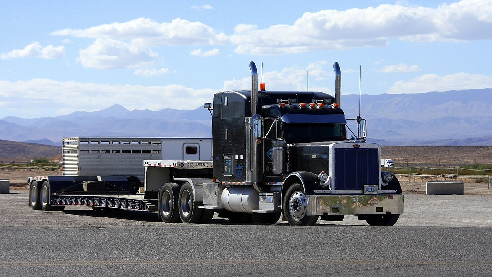 A large semi truck driving with mountain scenery in the background