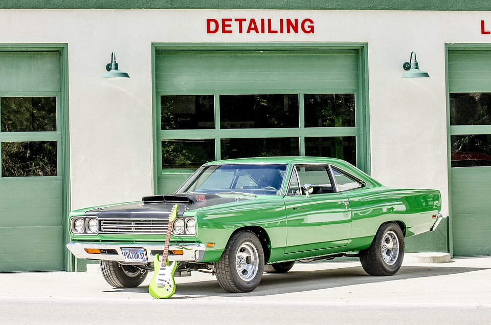 Green car sitting in front of a green garage