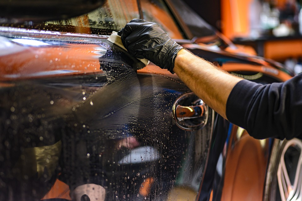 A hand polishing a orange body of a car