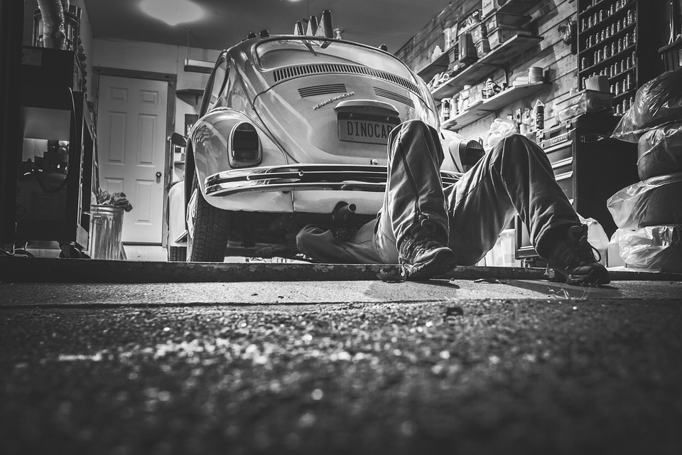 Black and white photo of a man underneath a old VW bug working on it