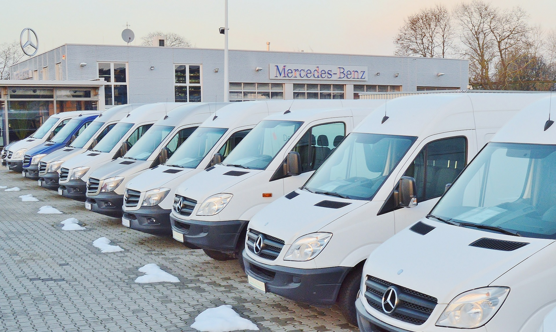 A fleet of white vans that are parked