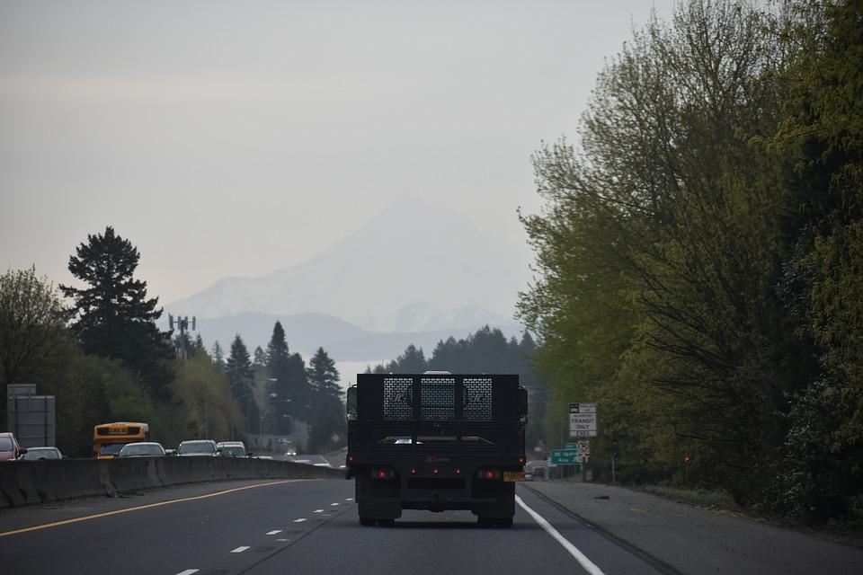 A cargo truck driving down a raining, foggy street