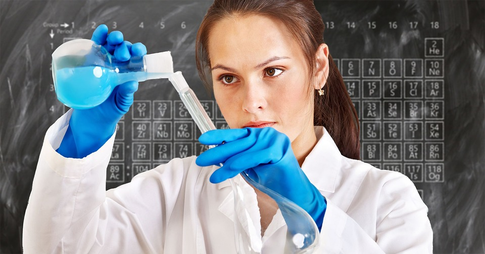 A scientist pouring a blue liquid into a container