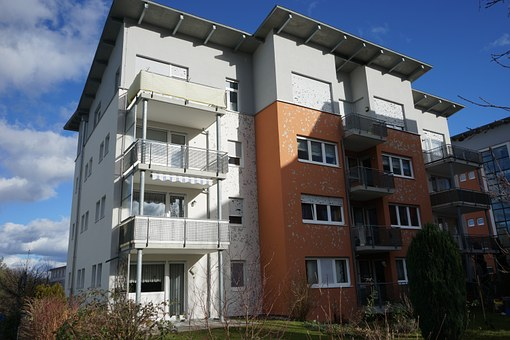 A tall white and orange apartment building