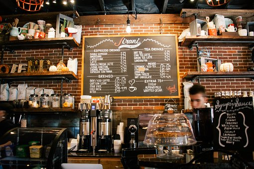 A cafe with a menu hanging that is written in chalk
