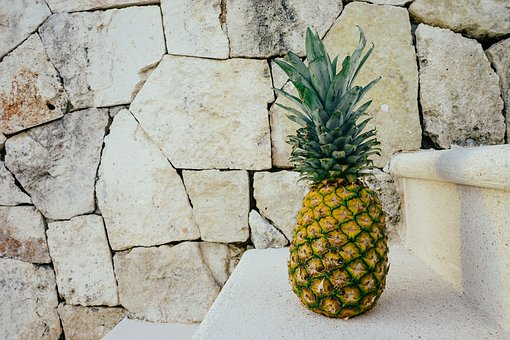 A pineapple against a rock wall, symbolizing hospitality