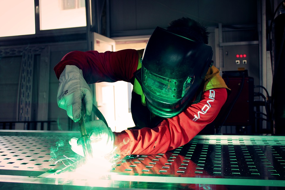 A welder hard at work welding with a green light at sparks being produced