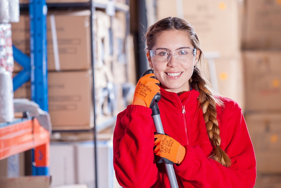 A working woman smiling at the camera while wearing safety glasses