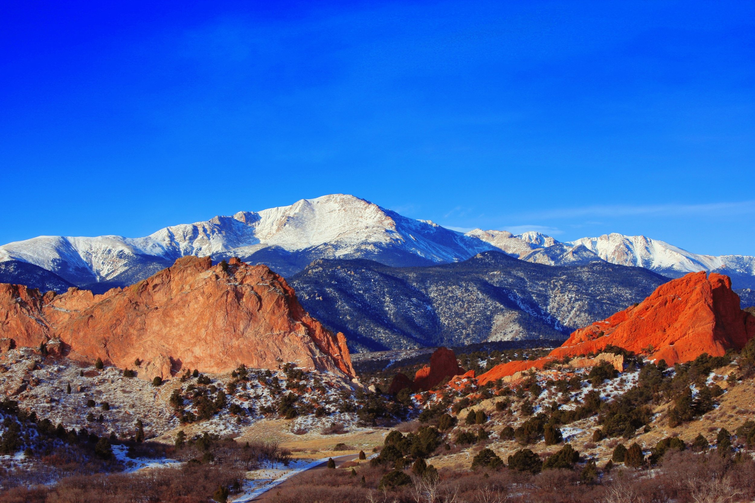 Landscape photo of Garden of the Gods and Pikes Peak lightly dusted with snow.