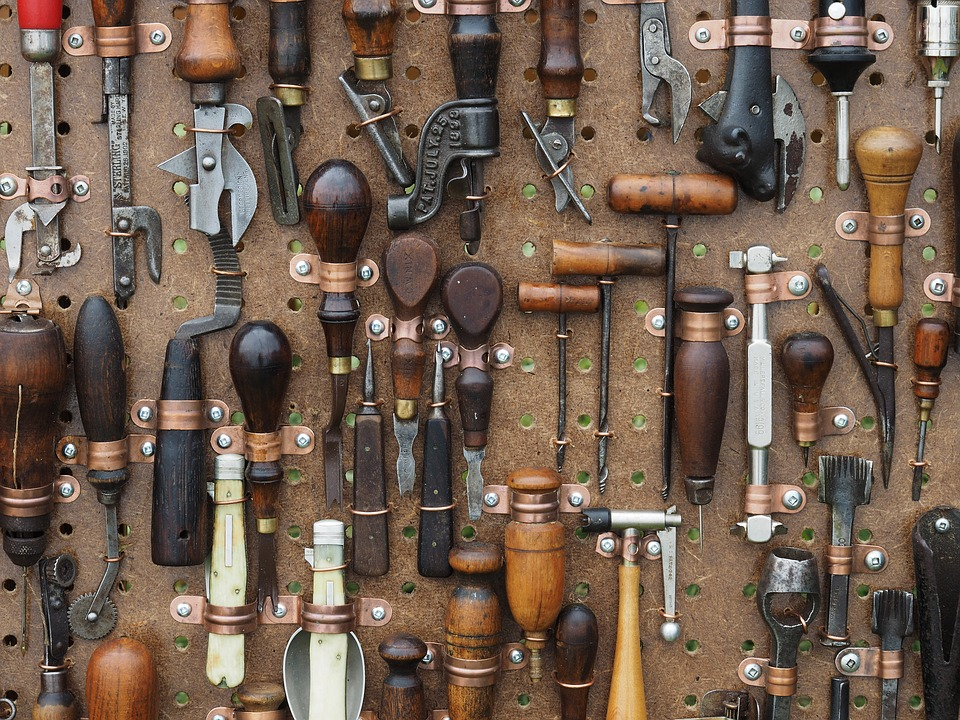 A wall filled with antique tools