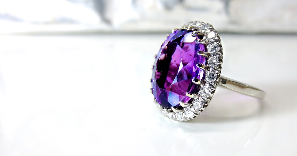 A up close shot of a ring with a large purple stone in the center