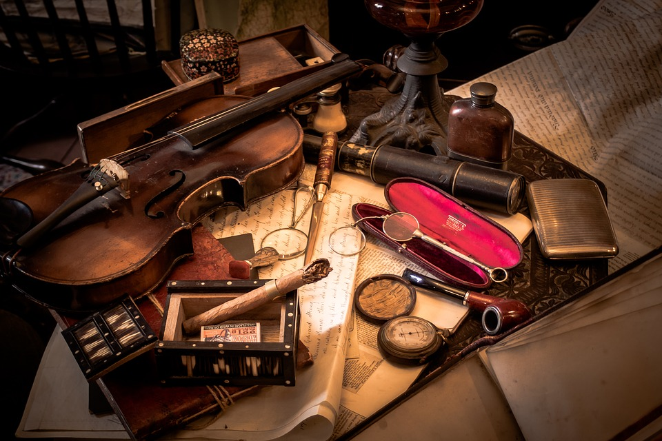 A collection of antique items that range from a violin to eye glasses to cigars
