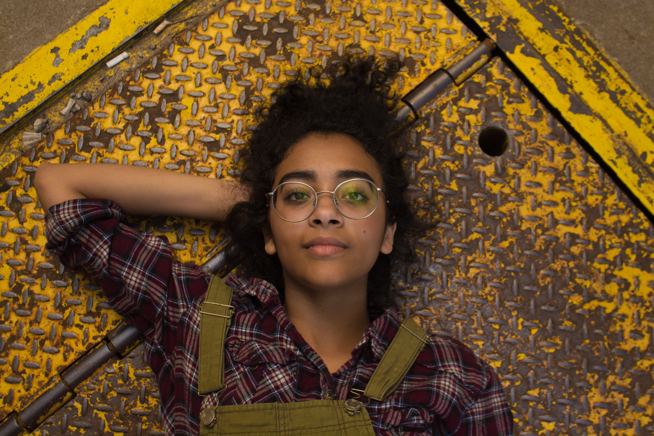 Working woman wearing glasses laying down on a rusted yellow metal floor
