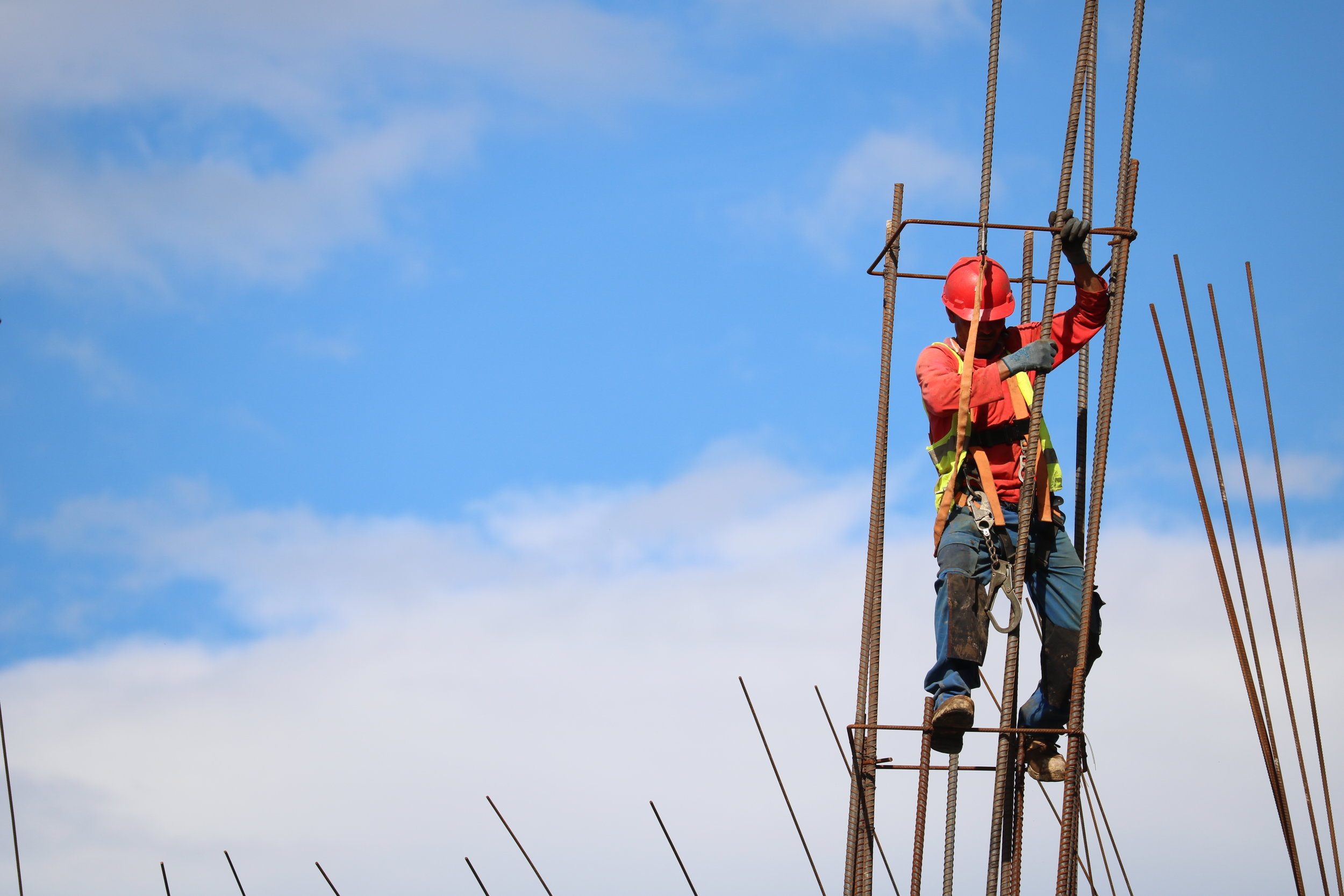 A construction man working on a piece of metal in front of a beautiful blue sky