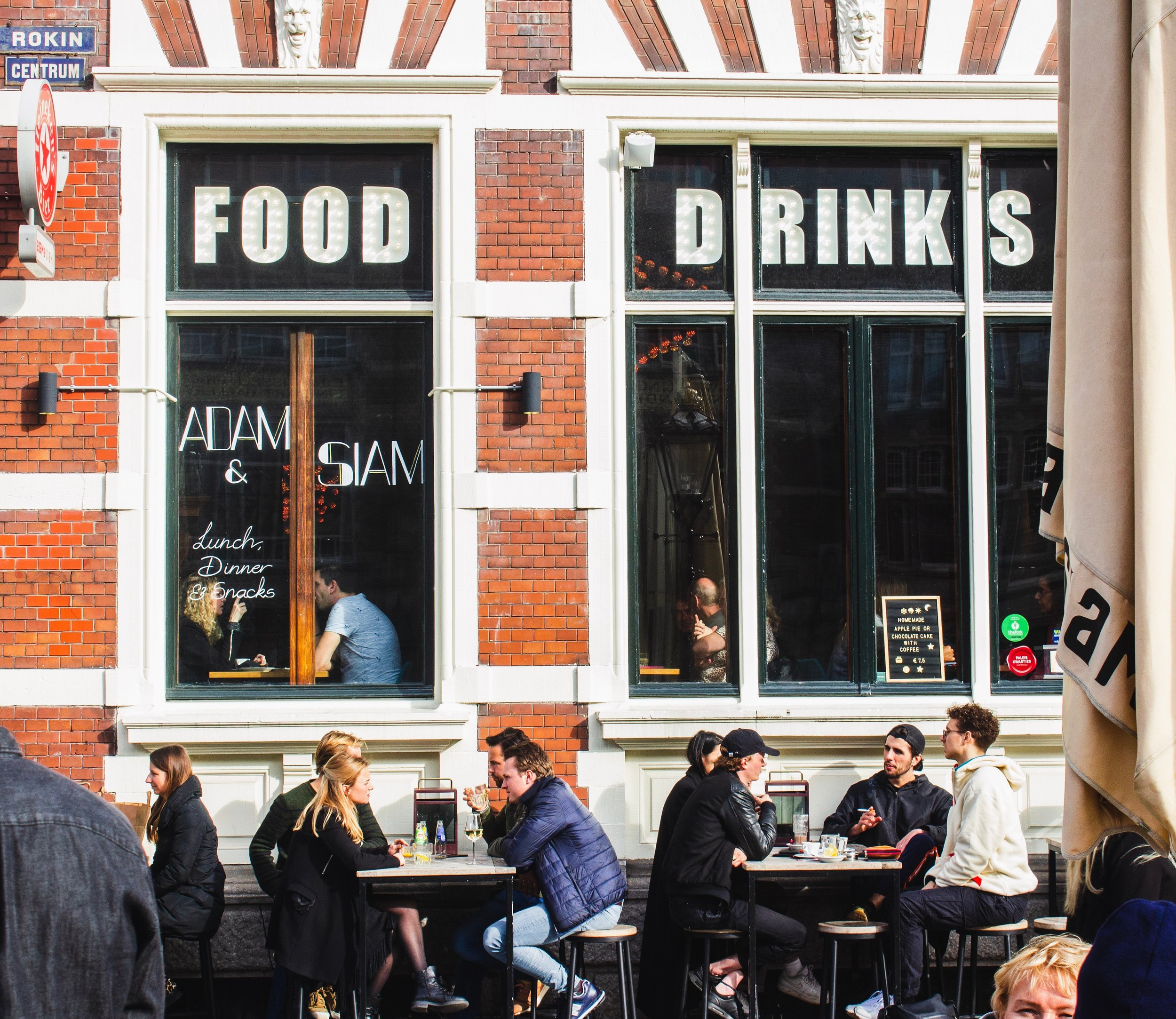 """A street view of people dining at tables on the street in front of a brick building with two big windows with the words """"FOOD, DRINKS"""" written on them"""