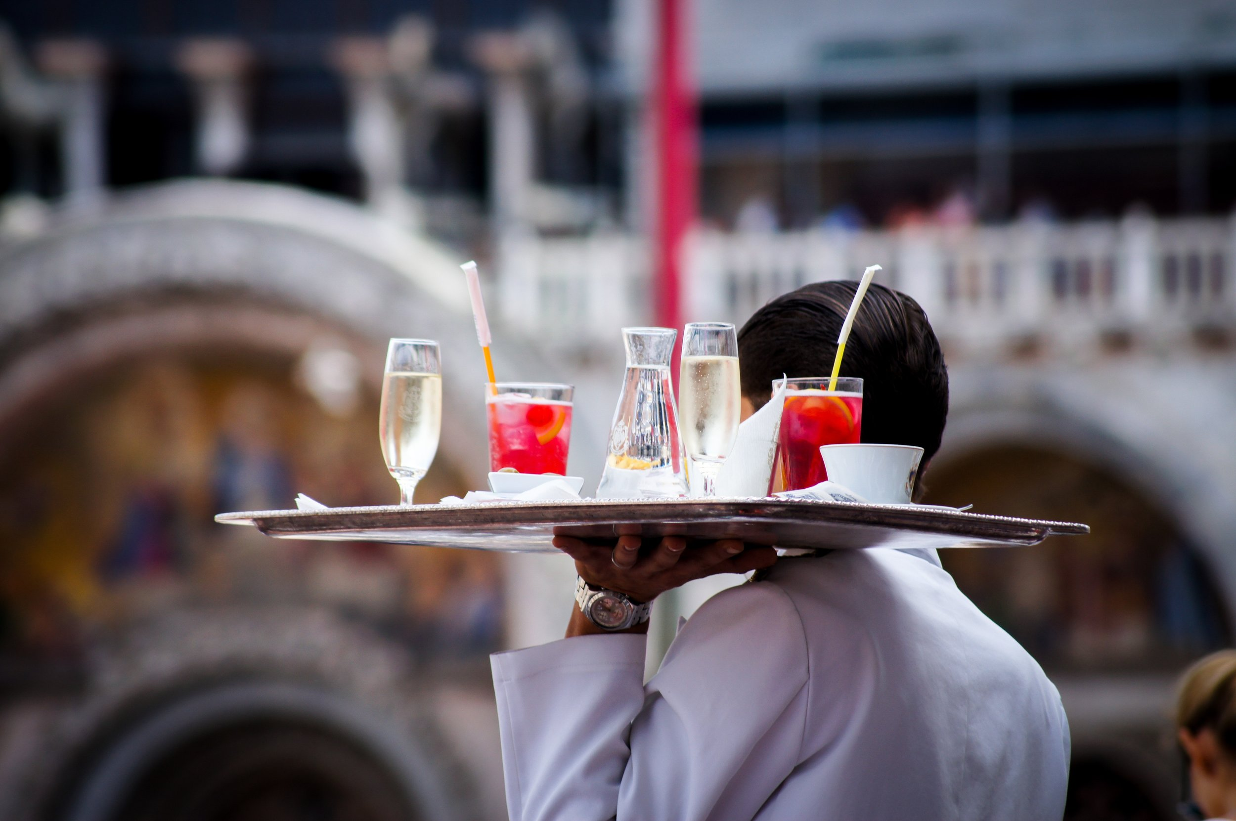 A waiter carrying a tray of drinks
