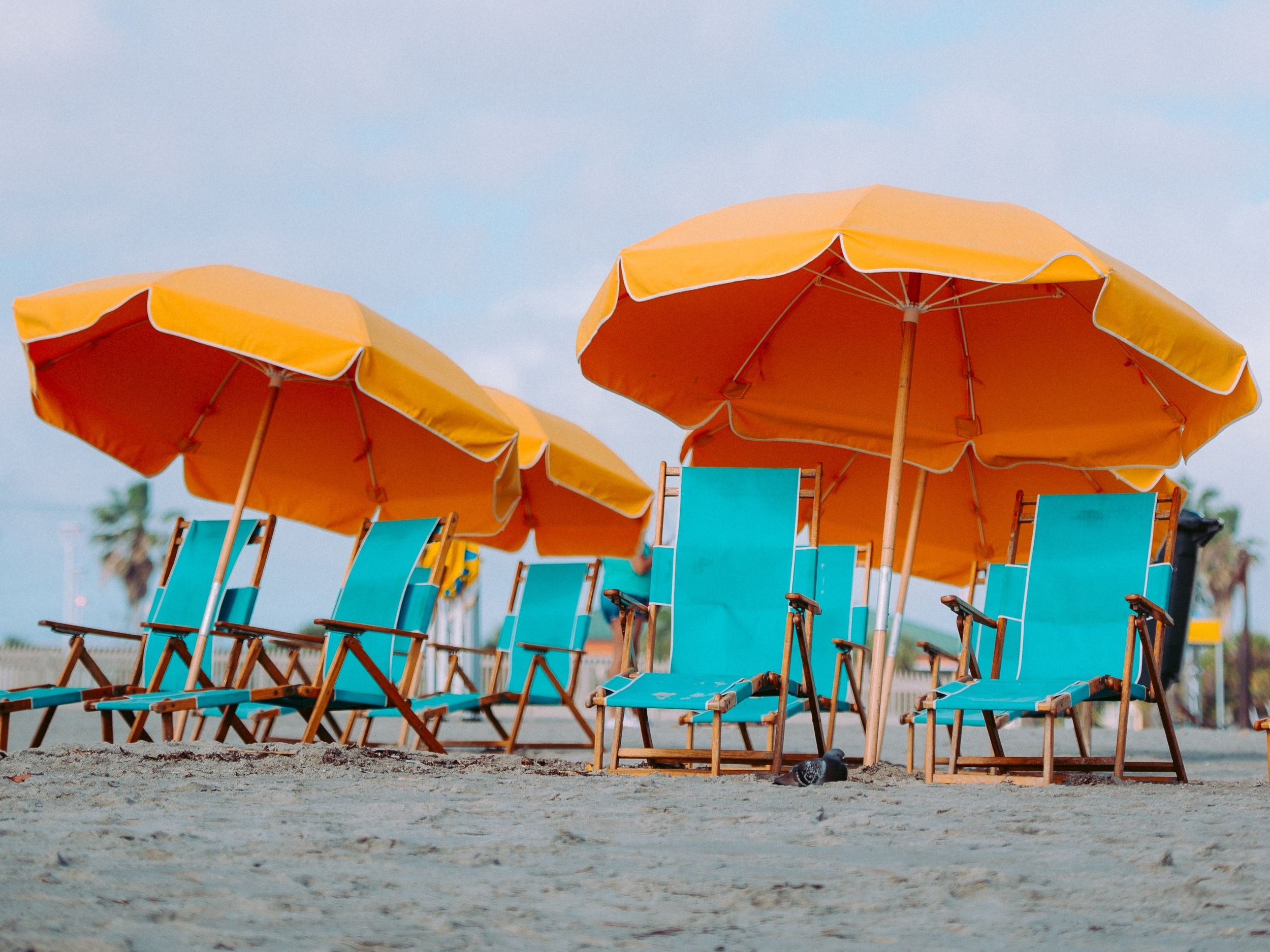 A beach setting with bright blue beach chairs shaded by bright yellow umbrellas