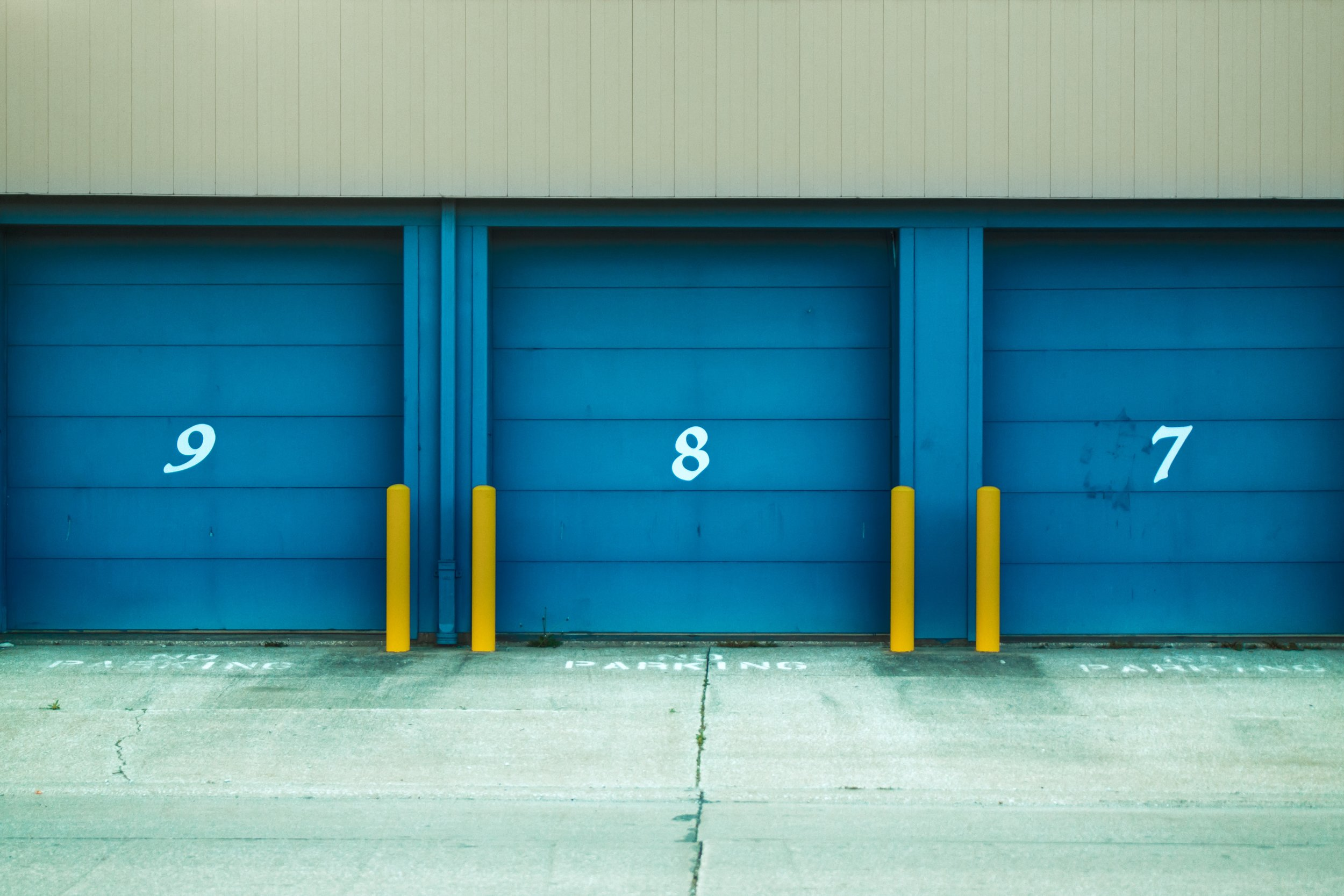 Three bright blue storage unit doors labeled 9, 8, and 7