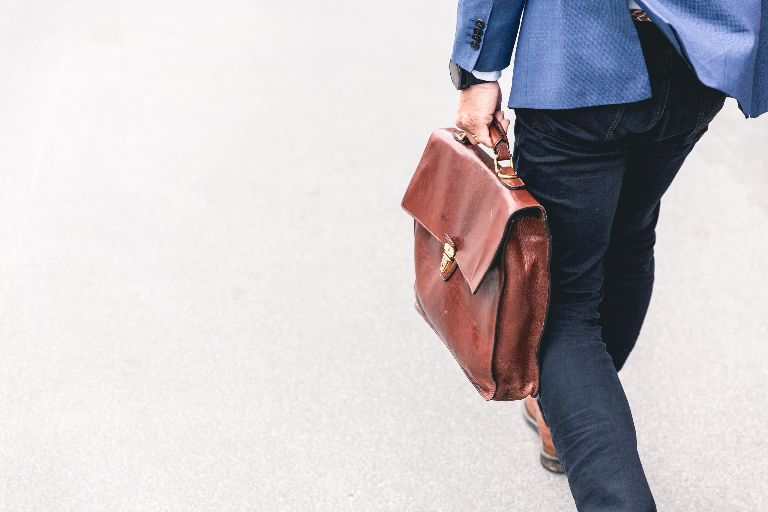 The bottom half of a man walking in jeans and a blazer while carrying a brief case