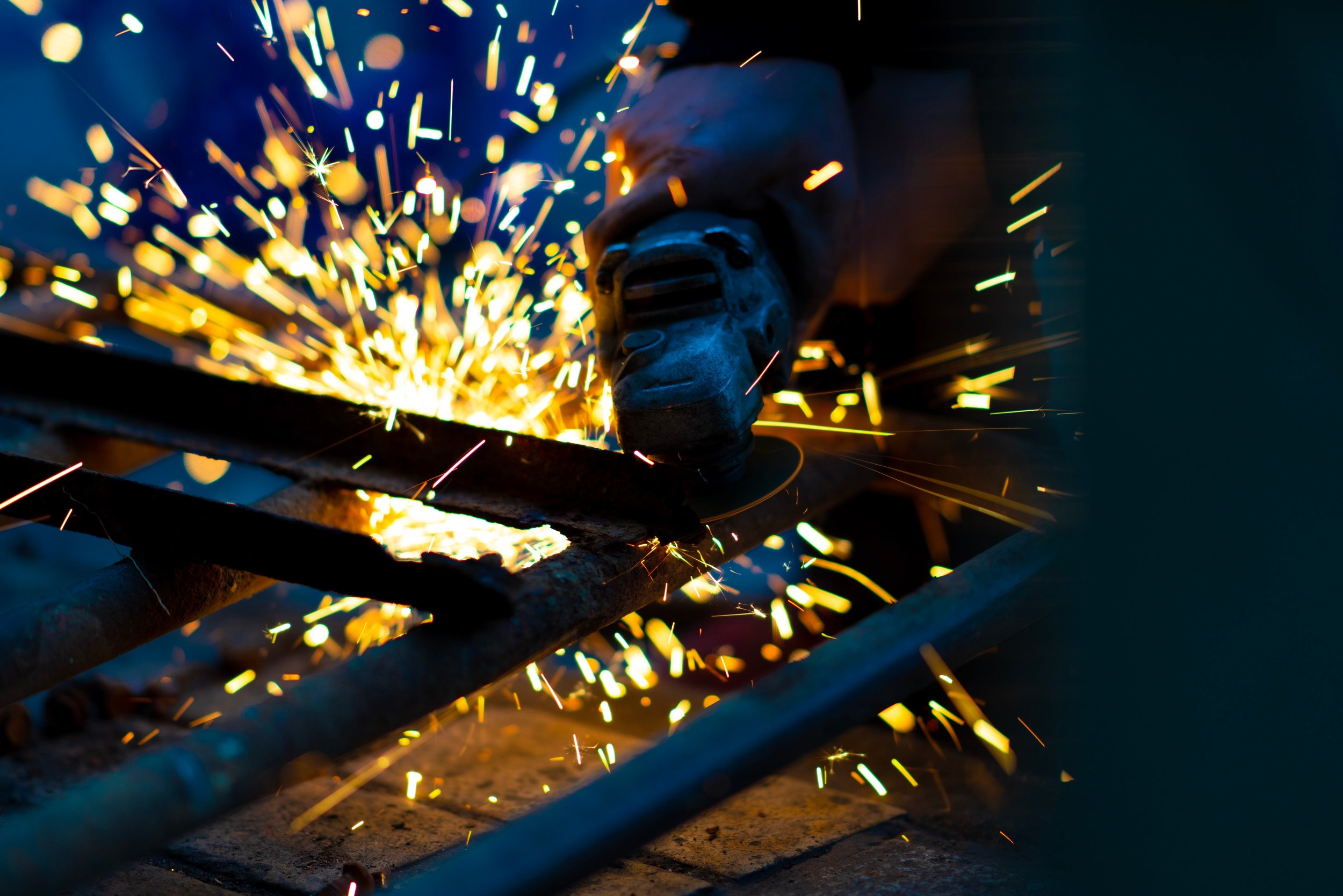 A close up shot of a person working on welding a piece of metal. Many sparks flying off the hot tool