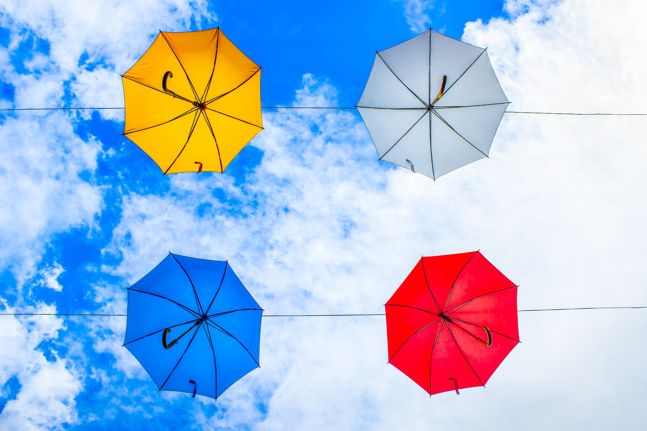 Four umbrellas from underneath that are yellow, blue, red, gray with a blue sky behind them