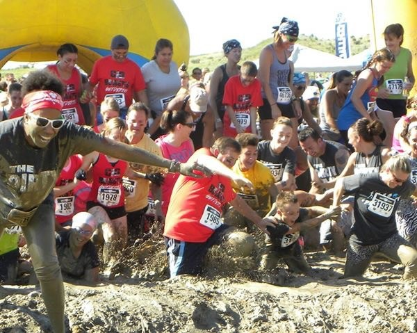 Bigfoot Insurance team members in red participating in a local Mud Run. C.E.O Martin Burlingame cheerfully falling into the mud.