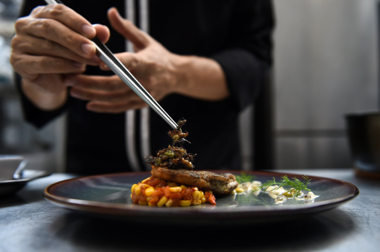 Edible winged ants are placed atop a fish fillet at Insects in the Backyard, a high-end bug-based bistro in Bangkok.  Lillian Suwanrumpha/AFP/Getty Images