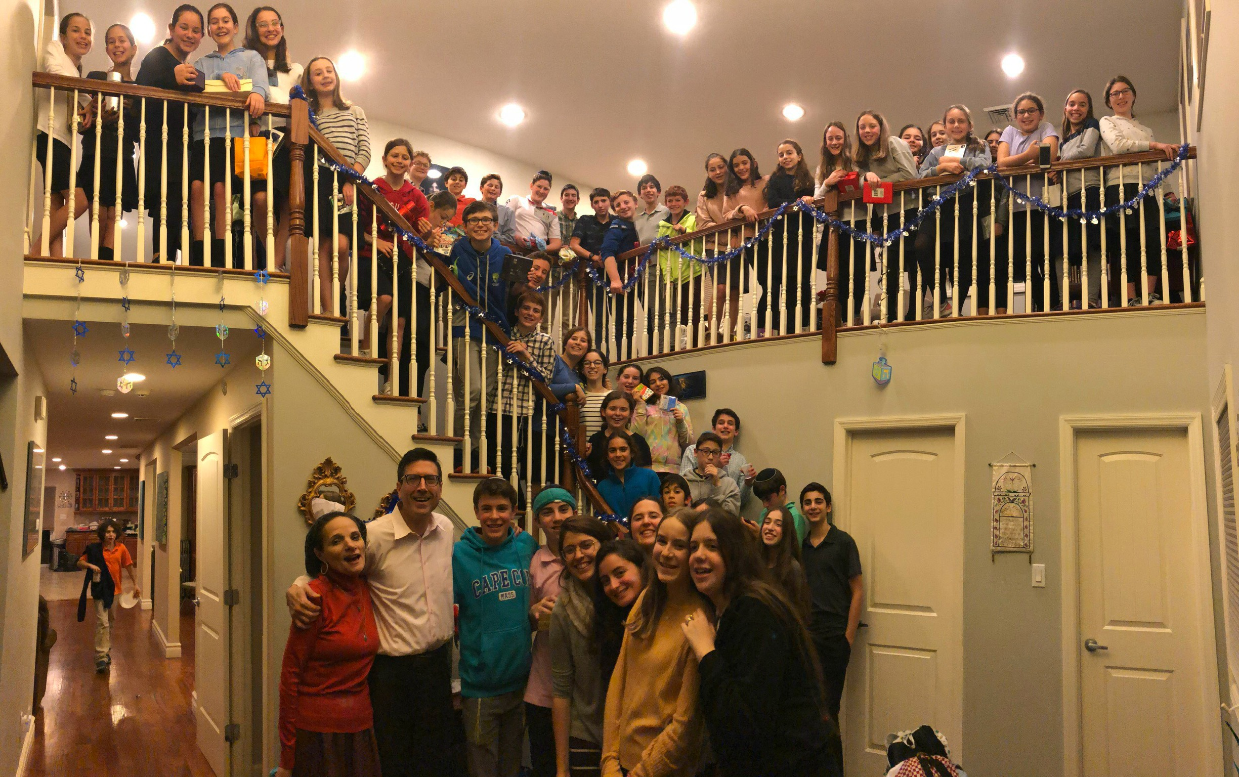 Current SAR Academy students celebrating Chanukah at the home of their teacher, Rabbi Steven Moskowitz AC '79
