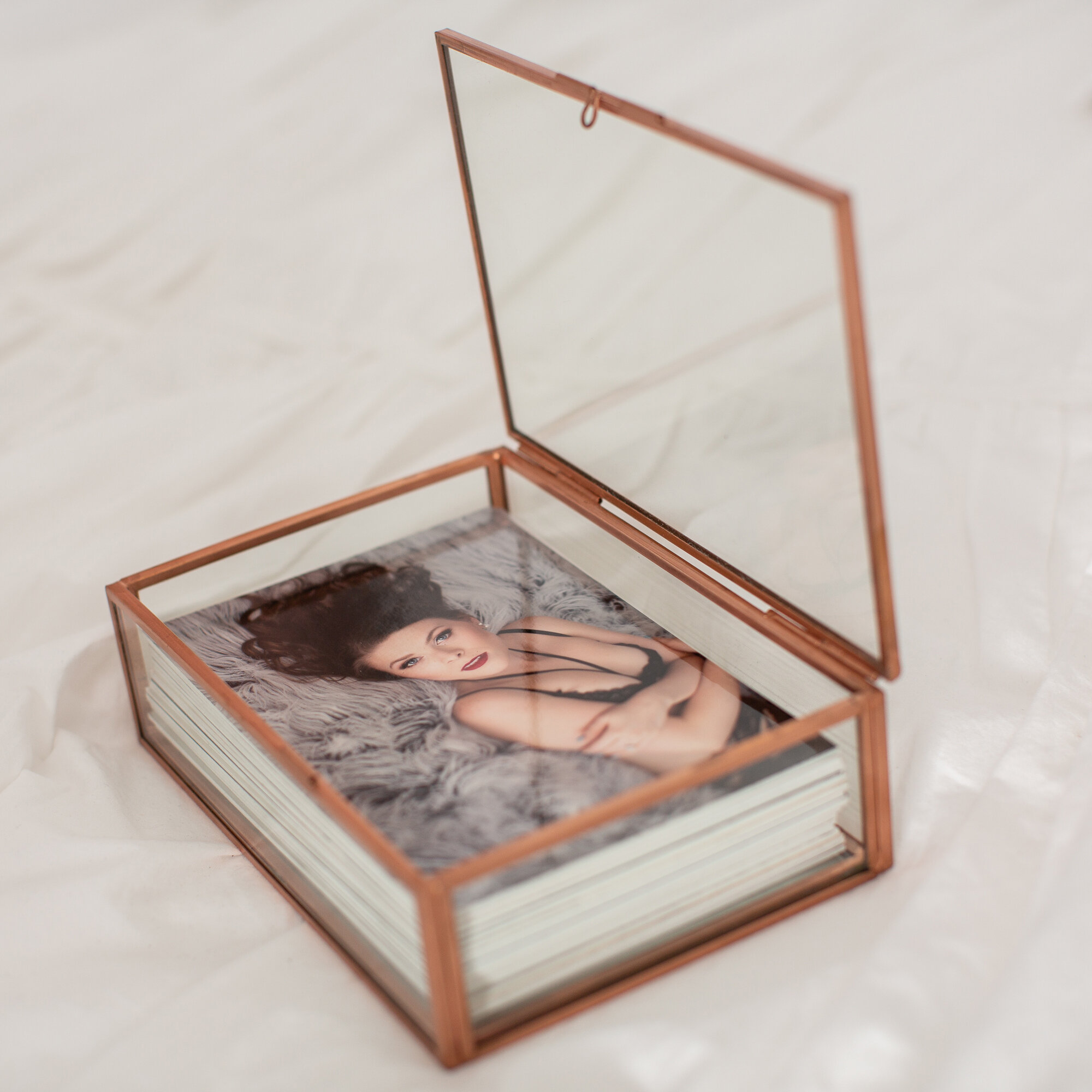 GLASS KEEPSAKE BOX - Stack of mounted photos inside of a glass box with rose gold accentsGlamorous vintage vibe