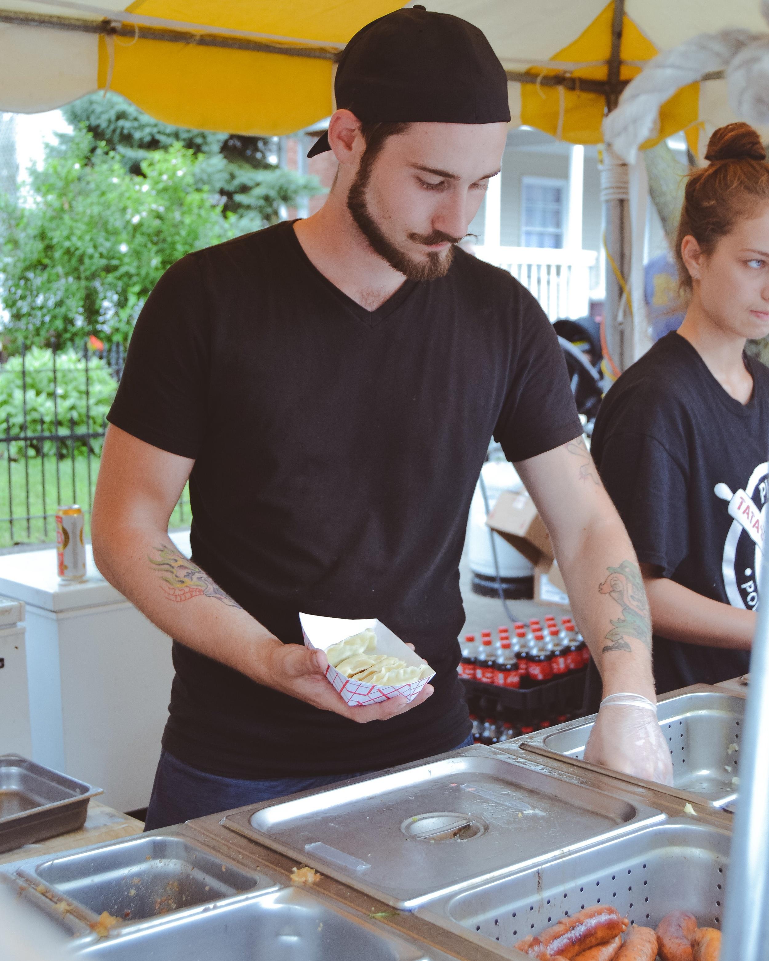 A vendor serves pierogi to a customer.  Photo by Hannah Rose Dominiak