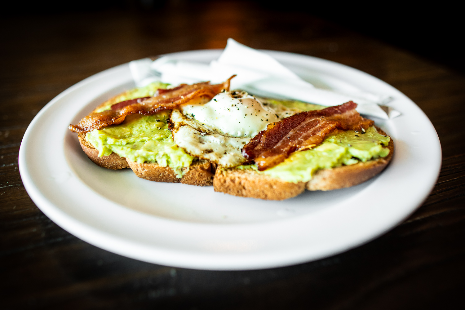 Avocado toast (served all day!) at Boulder Creek Coffee in Lawrenceville, GA. The avocado toast comes with sea salt, cracked paper, and bacon.