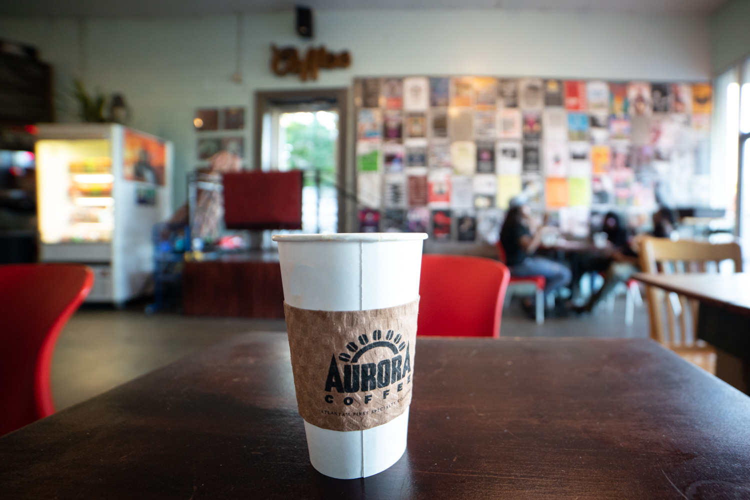 Coffee at Aurora. In the background: a full wall display of posters for local events, art shows, concerts, etc.