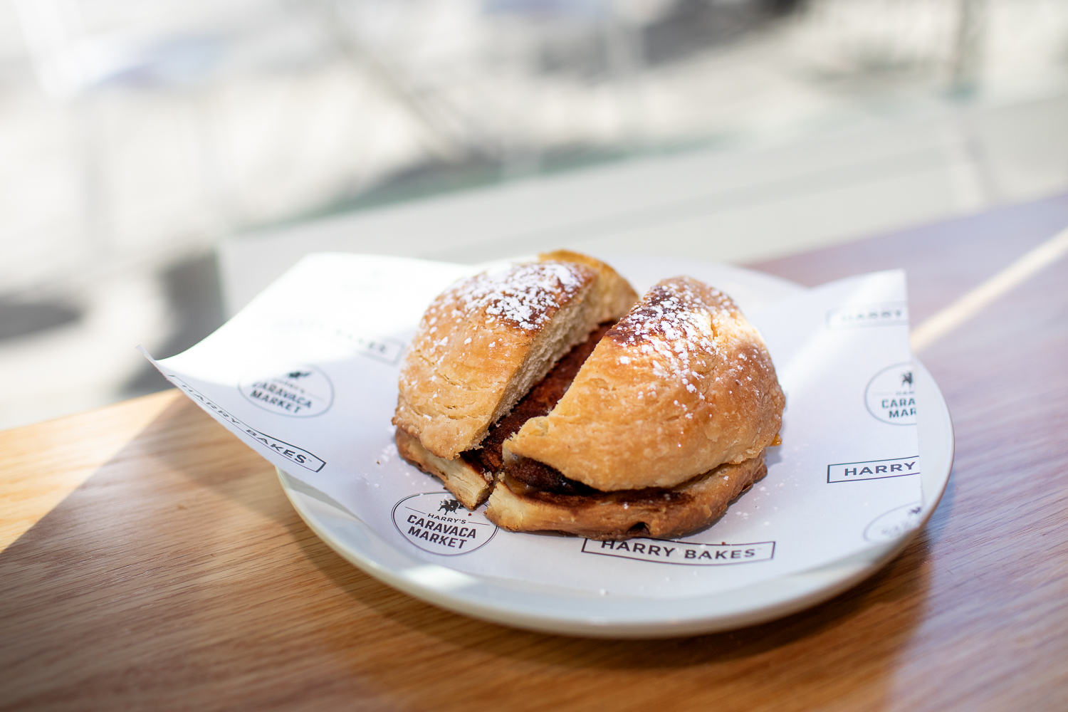 A chicken sandwich on Mallorca bread, topped with powdered sugar, at Harry Bakes Cafe.