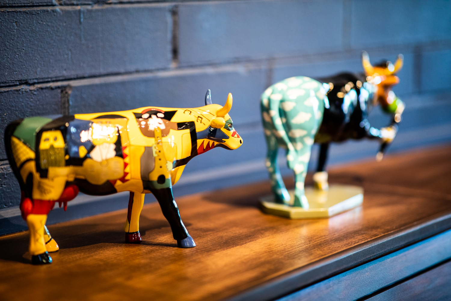Colorful cows—there are are a total of six on the back counter at Alchemist Trading Co. Can you guess what the homage is to with the cow standing on three feet in the background?