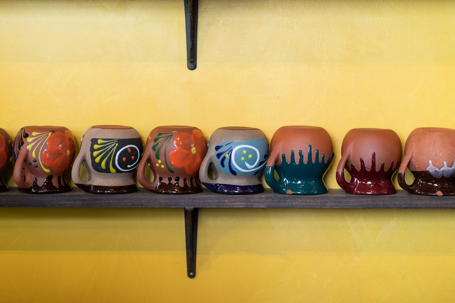On the shelves of El Tesoro are these Mexican taza de barro mugs, which are made of clay.