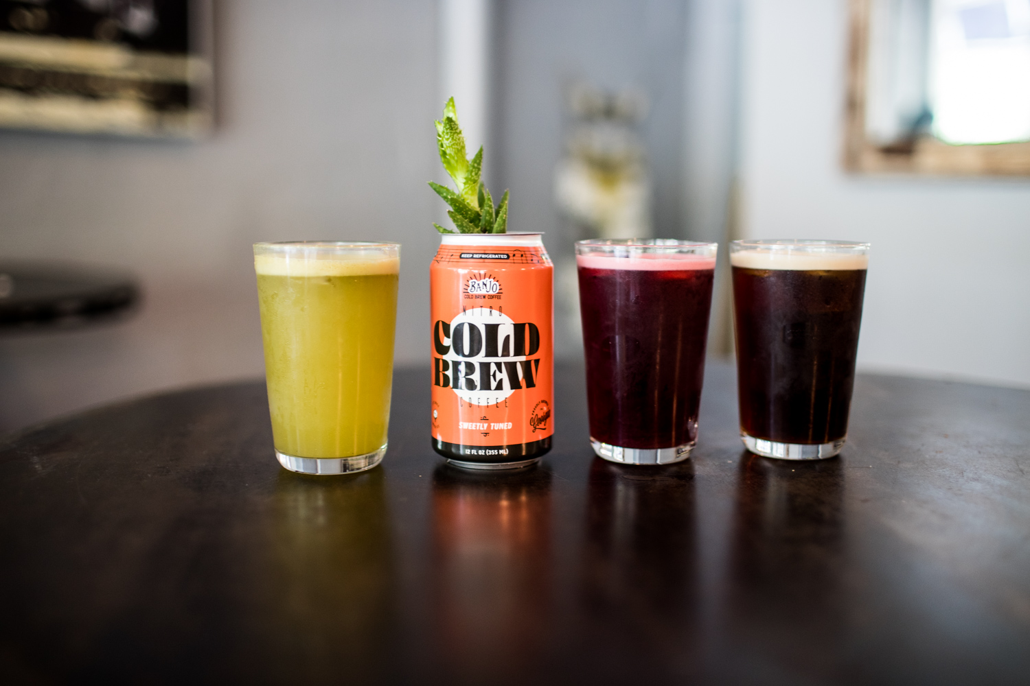 Left to right: matcha lemonade, a plant growing in a repurposed Banjo Cold Brew nitro can, hibiscus sour tea, and original nitro coffee.