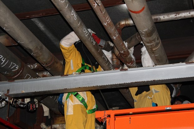 The prior manual method required technicians in protective clothing at elevation to deploy detectors. Note the marking and numbering of foot-long segments.